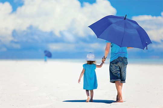 Dad & daughter on beach with umbrella